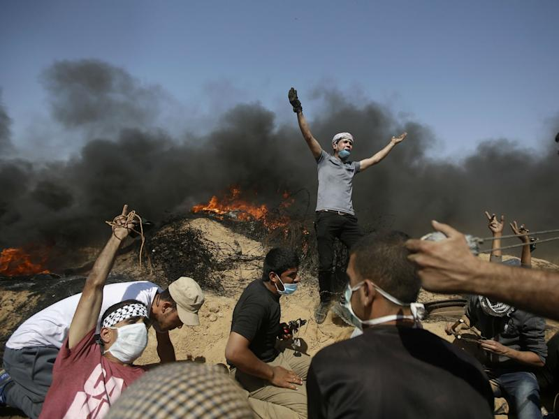 Palestinians take cover near the Gaza Strip's border with Israel during a protest in the Gaza Strip: AP Photo/Adel Hana