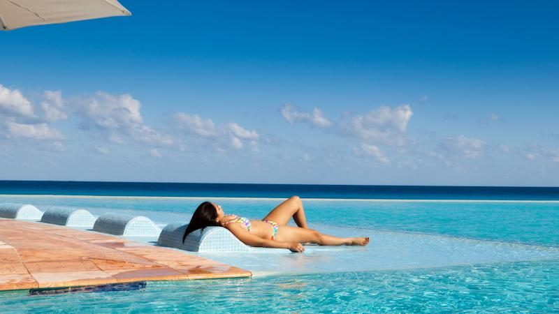 Young woman on a tourist resort vacation, relaxing by a tropical beach resort hotel infinity pool on the Caribbean Sea, Cancun, Riviera Maya, Mexico.