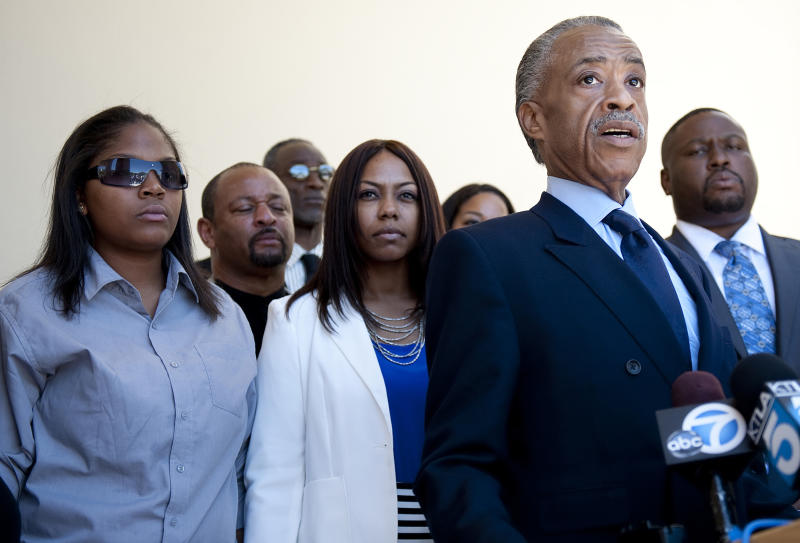 The Rev. Al Sharpton, foreground right, speaks to the reporters before the public memorial service for Rodney King at Forest Lawn-Hollywood Hills in Los Angeles on Saturday, June 30, 2012. King passed away earlier this month at 47. Behind Sharpton are King's daughters, Tristian King, and Laura Dene King.  (AP Photo/Grant Hindsley)