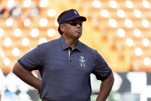 File-This Sept. 1, 2018, file photo shows Navy head coach Ken Niumatalolo looking on as his team warms up before an NCAA college football game in Honolulu. Navy has one of the most productive running attacks in the nation, ranking third behind Georgia Teach and Army at 286.9 yards per game. The bad news is the Midshipmen are coming off being held to a season-low 124 yards on the ground in the 42-0 loss to Cincinnati. We've never been beat like that,'' Niumatalolo said. (AP Photo/Eugene Tanner, File)