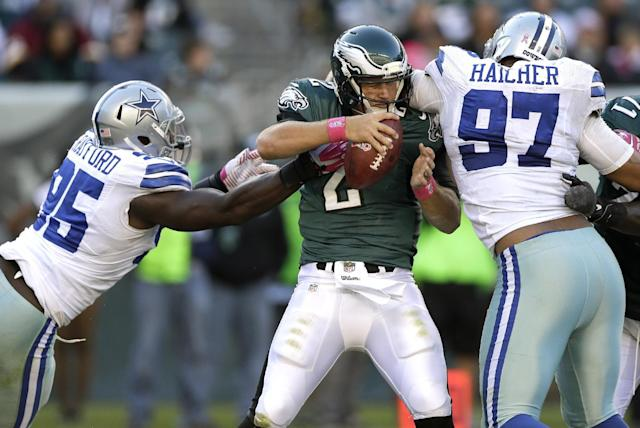 Philadelphia Eagles quarterback Matt Barkley, center, is pressured by Dallas Cowboys defensive end Caesar Rayford, left, and defensive tackle Jason Hatcher, right, during the second half of an NFL football game, Sunday, Oct. 20, 2013, in Philadelphia. The Cowboys won 17-3. (AP Photo/Matt Rourke)