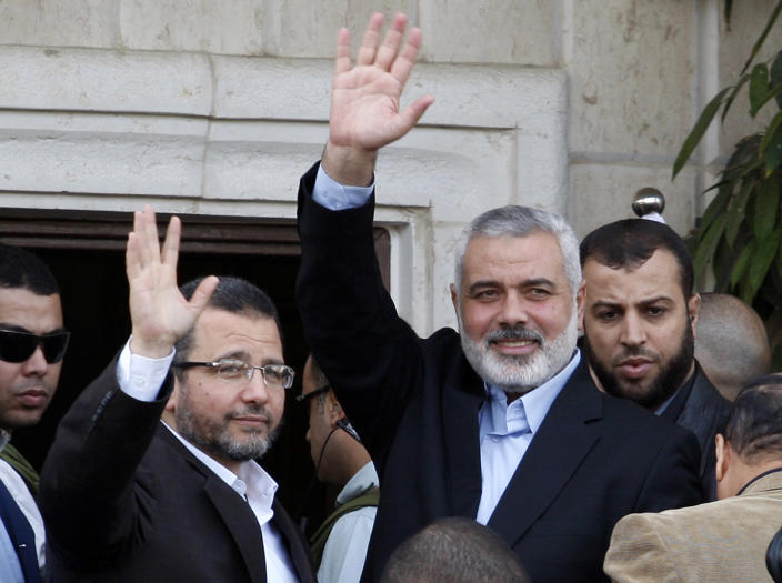 Gaza's Hamas Prime Minister Ismail Haniyeh, right, and Egyptian Prime Minister Hesham Kandil, left, wave to the crowd as they meet in Gaza City, Friday, Nov. 16, 2012. Israel offered to suspend its offensive in the Gaza Strip on Friday during a brief visit by Egypt's premier there if militants refrain from firing rockets at Israel, an official said, but the Palestinians unleashed a fresh salvo.(AP Photo/Adel Hana)