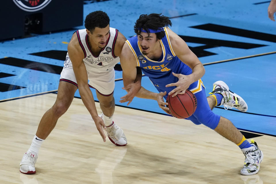UCLA guard Jaime Jaquez Jr. (4) picks up a loose ball ahead of Gonzaga guard Jalen Suggs, left, during the first half of a men's Final Four NCAA college basketball tournament semifinal game, Saturday, April 3, 2021, at Lucas Oil Stadium in Indianapolis. (AP Photo/Darron Cummings)