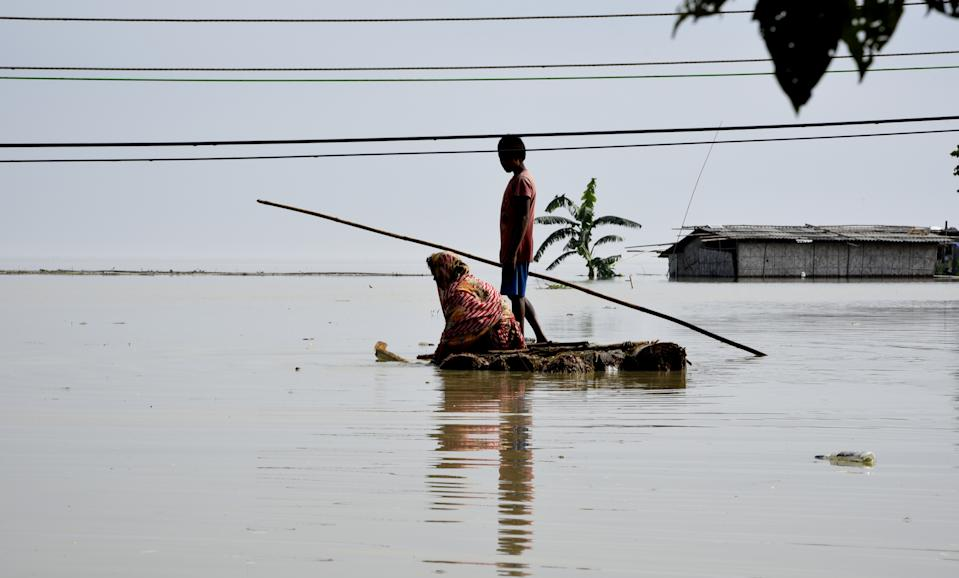 Villagers cross a flooded area on a makeshift raft, in Panikhaiti village, in Kamrup District, Assam, India on Tuesday, on July 14, 2020. Villages in Assam were flooded due to heavy rains. The rising water level inundated houses, residents were forced to move to a safer place. (Photo by Hafiz Ahmed/Anadolu Agency via Getty Images)