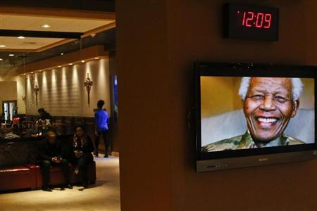 Mandela is pictured on a display screen as people attend a tribute service for him at the Christian Cultural Center in New York