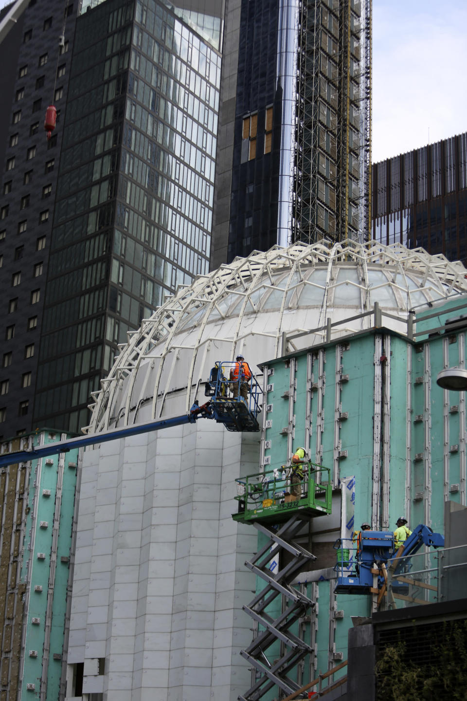 Workers install marble on the exterior of St. Nicholas Greek Orthodox Church and National Shrine, the only house of worship on ground zero, on Thursday, July 22, 2021, in New York. Through an innovative process, interior lights are being designed to illuminate thin panels of marble mined from the same Pentelic vein in Greece that sourced the Parthenon, the ancient temple in Athens. The shrine will have a ceremonial lighting on the eve of the 20th anniversary of the Sept. 11, 2001 attacks, while the interior is slated for completion next year. (AP Photo/Jessie Wardarski)