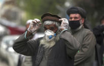 FILE - In this April 20, 2020, photo, daily-wage workers wear protective face mask to help curb the spread of the coronavirus in Kabul, Afghanistan. A prominent international aid organization warned Tuesday, June 2, 2020 that Afghanistan is on the brink of a humanitarian disaster because the government is unable to test at least 80% of possible coronavirus cases. (AP Photo/Rahmat Gul, File)