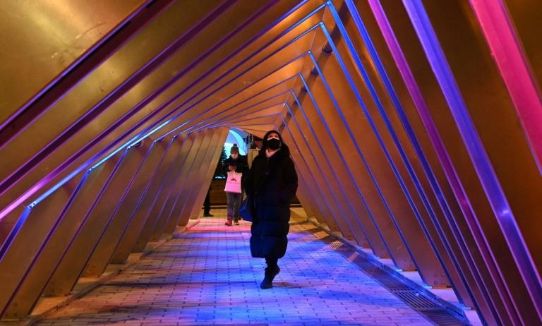 People walk through the 'Iceberg' sound-and-light installation on December 18, 2020 in Montreal, Quebec, one of the five light installations on display to bring some comfort to residents of a city that has been battered by months of coronavirus