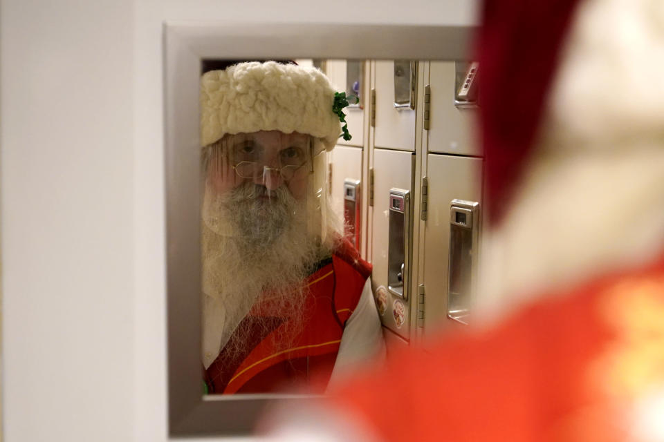 Brad Six, wearing a protective face shield, looks in the mirror as he prepares to work as Santa Claus at Bass Pro Shops, Friday, Nov. 20, 2020, in Miami. This is Santa Claus in the Coronavirus Age, where visits are done with layers of protection or moved online. Putting hundreds of kids a day onto your lap to talk directly into your face — that's not happening. (AP Photo/Lynne Sladky)