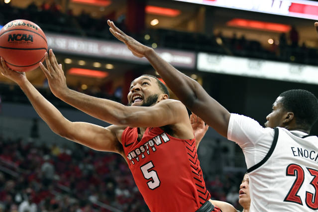 Youngstown State guard Christian Bentley (5) attempts a layup around the defense of Louisville center Steven Enoch (23) during the first half of an NCAA college basketball game in Louisville, Ky., Sunday, Nov. 10, 2019. (AP Photo/Timothy D. Easley)