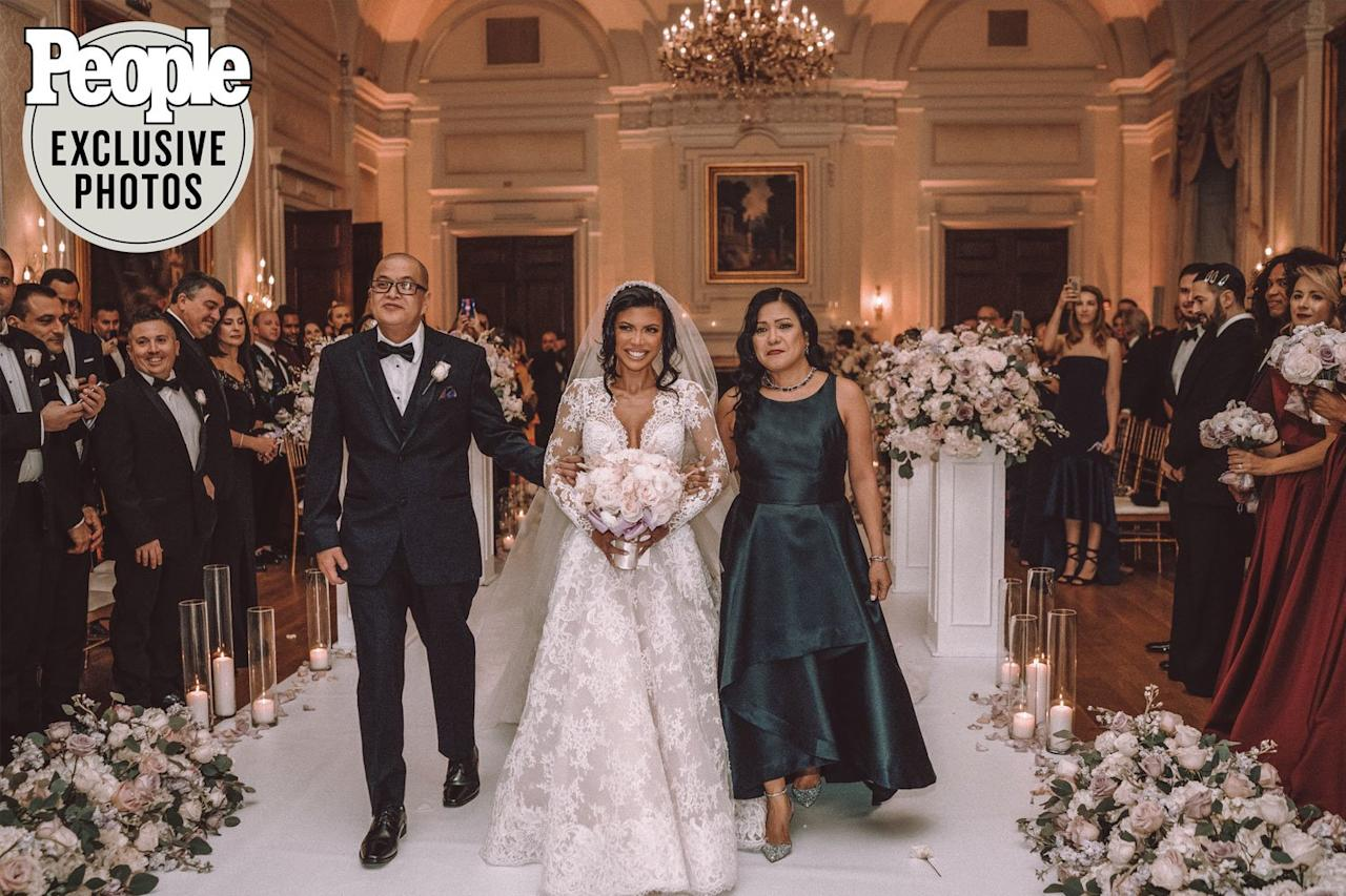 """The bride was walked down the aisle, which was decorated with candles and flowers, by her mother, Nelia, and father, James, as the band Music Travel Love sang """"Can't Help Falling in Love."""""""