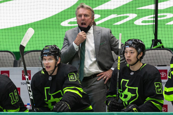 """FILE - Dallas Stars coach Rick Bowness gives direction to the team during the second period of an NHL hockey game against the Columbus Blue Jackets in Dallas, in this Saturday, April 17, 2021, file photo. After winning four in a row at home to get within a point of the final playoff spot in the Central Division, the Stars now will end the regular season playing nine of their last 11 games on the road. They will travel to five different cities in that 20-day stretch. """"We've known all along it was coming,"""" coach Rick Bowness said. (AP Photo/Sam Hodde, File)"""