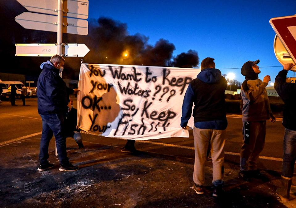 <p>French fishermen in Boulogne-sur-Mer hold a banner as they block lorries carrying UK-landed fish</p> (Reuters)