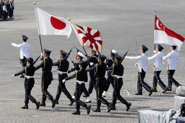 <p>Singaporean and Japanese troops march with flags during the traditional Bastille Day military parade on the Champs-Élysées on July 14, 2018, in Paris, France. (Photo: Thierry Chesnot/Getty Images) </p>