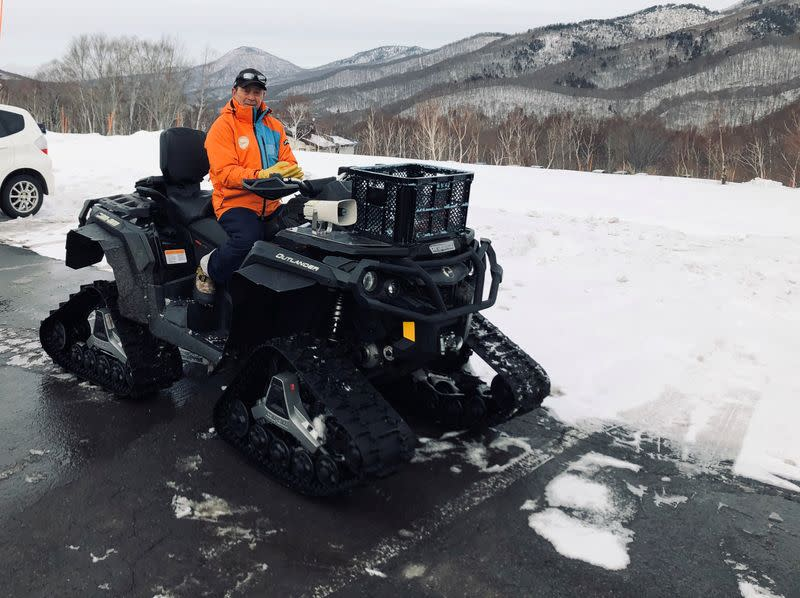 Masami Yashima, manager of Okushiga Kogen snow resort, sits on a snow quad in a car park in the winter season in Nagano