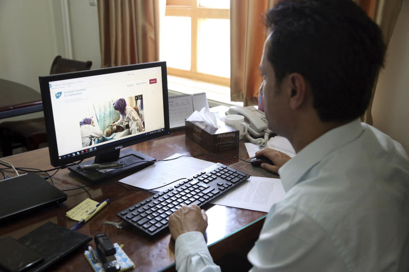 Ahmad Khalid Fahim, program director for the Swedish Committee for Afghanistan shows the group's website during an interview with The Associated Press in Kabul, Afghanistan, Wednesday, July 17, 2019. The Swedish non-governmental organization in Afghanistan said the Taliban have forced the closure of 42 health facilities run by the non-profit group in eastern Maidan Wardan province. (AP Photo/Rahmat Gul)