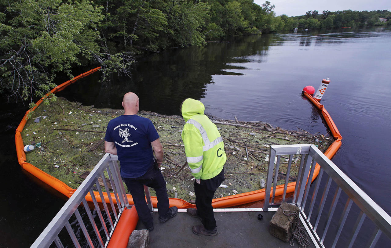 """<p>Activist Rocky Morrison, left, and volunteer Dalton Abbott, of the """"Clean River Project"""" examine a boom filled with waste collected from a recovery boat on the Merrimack River in Chelmsford, Mass. Syringes left by drug users amid the heroin crisis are turning up everywhere. They hide in weeds along hiking trails and in playground grass, get washed into rivers and onto beaches, and lie scattered about in baseball dugouts and on sidewalks and streets. There are reports of children finding them and getting poked. (Photo: Charles Krupa/AP) </p>"""