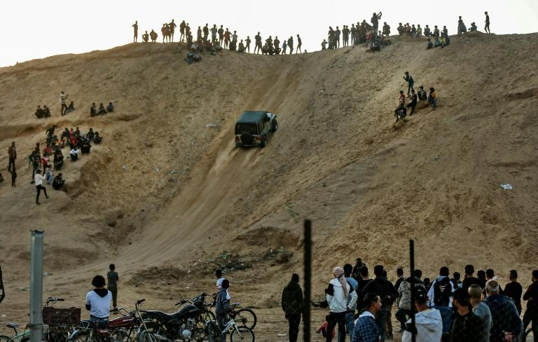Spectators watch as a Palestinian rides his jeep up a sandy hill during a weekly show in the Al-Zahra area near Gaza City