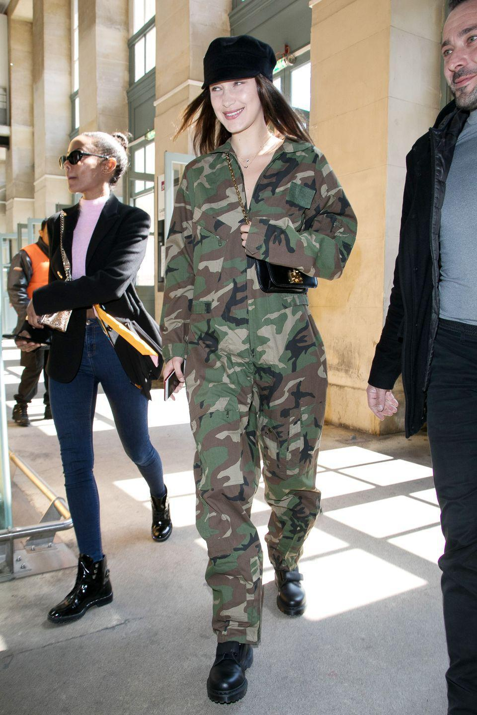 <p>In a camo jumpsuit, black hat and black leather boots while out in London. </p>
