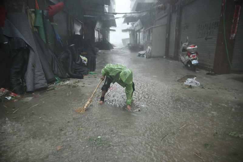 A man dredges a sewer on August 8, 2015, as Typhoon Soudelor brought heavy rain to Ningde, eastern China (AFP Photo/)
