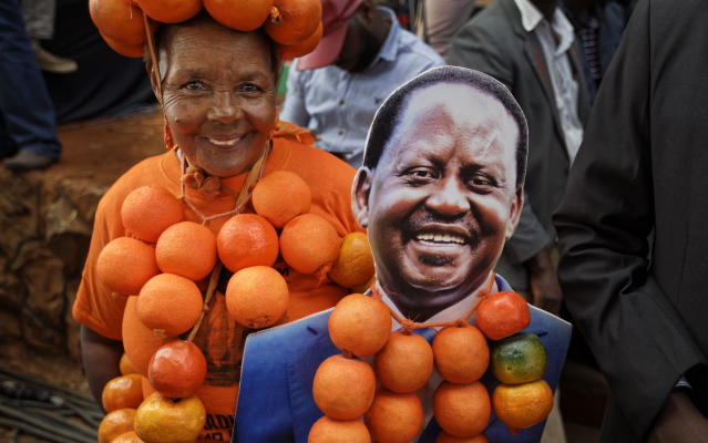 <p>A supporter of opposition leader Raila Odinga wears oranges, the party's symbol and color, and holds a placard of Odinga, at his final electoral campaign rally in Uhuru Park in downtown Nairobi, Kenya, Saturday, Aug. 5, 2017. (Photo: Ben Curtis/AP) </p>