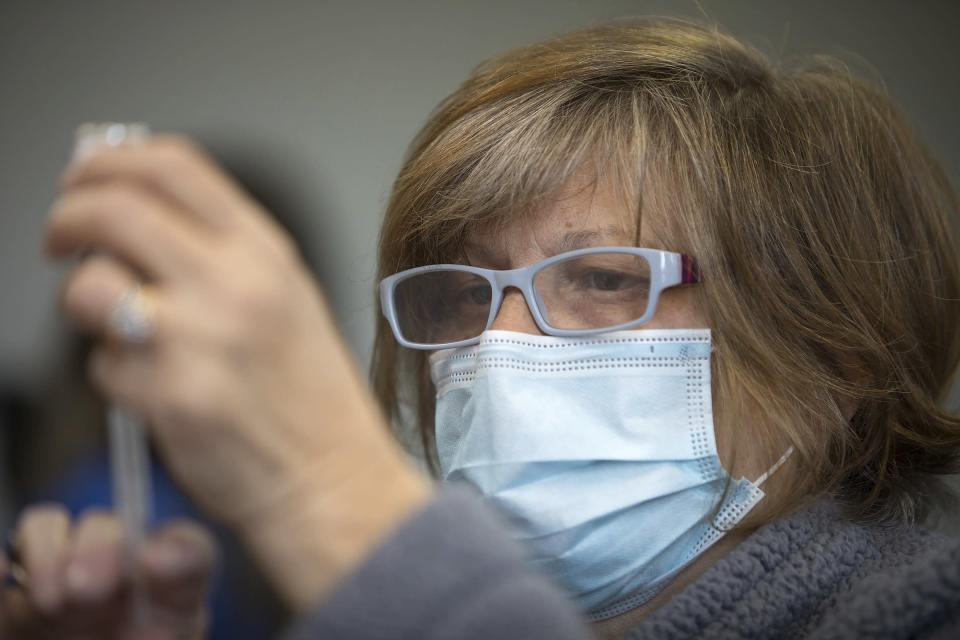 Sue Mason fills a syringe with a dose of the Moderna COVID-19 vaccine inside of the pharmacy station at the Hamilton County Health Department's new COVID Vaccination POD at the CARTA Bus Terminal on Thursday, Jan. 28, 2021 in Chattanooga, Tenn. (Troy Stolt/Chattanooga Times Free Press via AP)