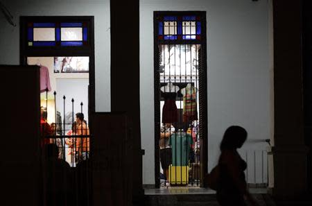 A woman walks past a private boutique set up at the entrance of a home in Havana