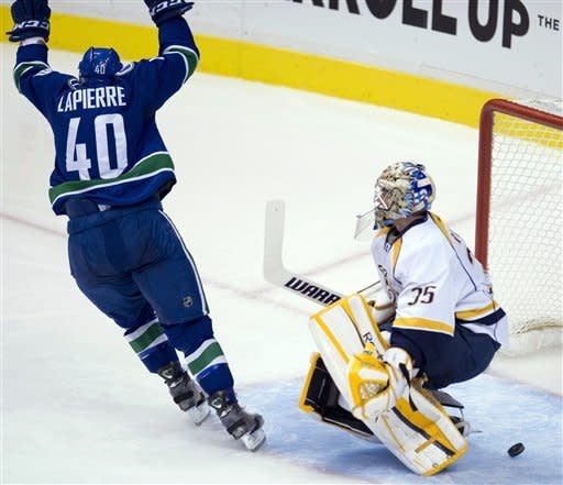 Vancouver Canucks center Maxim Lapierre (40) celebrates his goal against Nashville Predators goalie Pekka Rinne (35) during the second period of their NHL hockey game, Thursday, March,14, 2013, in Vancouver. (AP Photo/The Canadian Press, Jonathan Hayward)