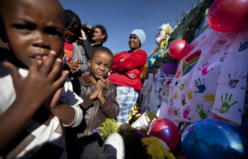 Children from a creche pray for the health of Nelson Mandela outside the entrance to the Mediclinic Heart Hospital where former South African President Nelson Mandela is being treated in Pretoria, South Africa Friday, June 28, 2013. Nelson Mandela's health improved overnight and although his condition remains critical it is now stable, the South African government said on Thursday. (AP Photo/Ben Curtis)