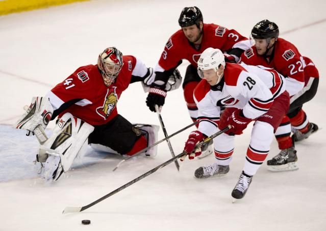 Carolina Hurricanes Alexander Semin tries to handle the puck past Ottawa Senators goalie Craig Anderson under pressure from Marc Methot (3) and Erik Condra (22) during second period NHL action Monday March 31, 2014 in Ottawa. (AP Photo/The Canadian Press, Adrian Wyld)