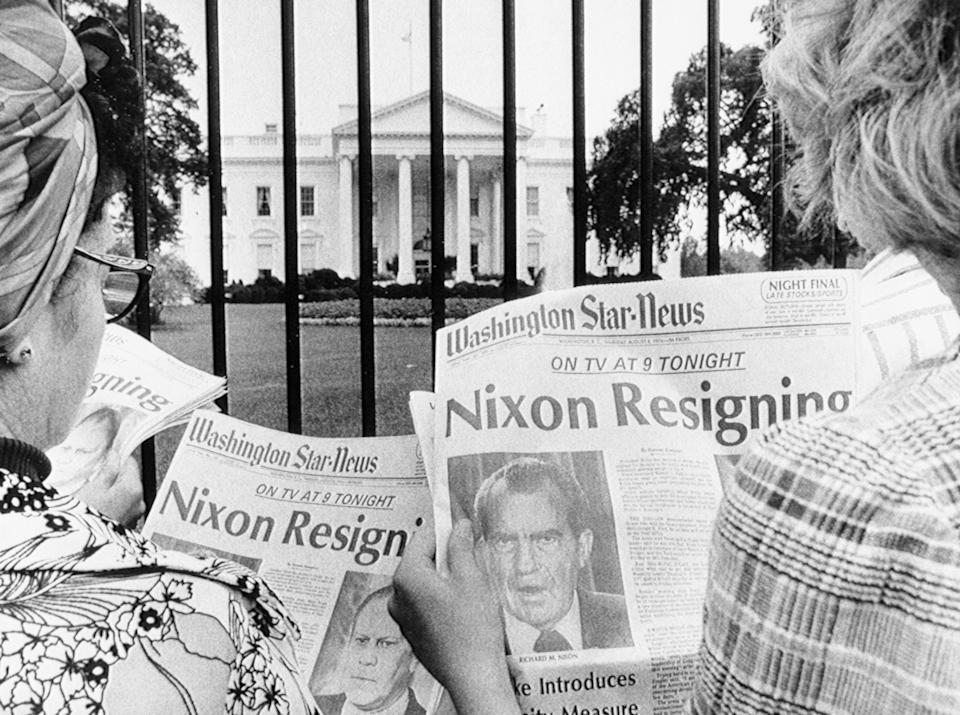 8/8/1974-Washington, DC- Newspaper headlines being read by tourists in front of the White House tell of history in the making. (Bettmann Archive/Getty Images)