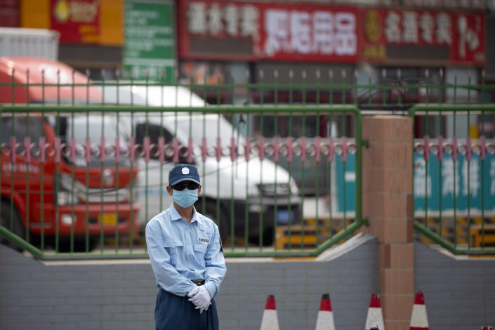 A security officer stands guard outside the Xinfadi wholesale food market district in Beijing, Saturday, June 13, 2020. Beijing closed the city's largest wholesale food market Saturday after the discovery of seven cases of the new coronavirus in the previous two days. (AP Photo/Mark Schiefelbein)