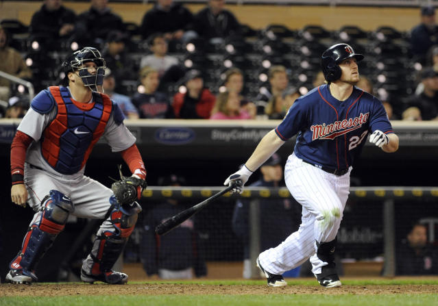 Minnesota Twins' Chris Parmelee watches his two-run home run in front of Boston Red Sox catcher A.J. Pierzynski during the ninth inning of a baseball game in Minneapolis, Tuesday, May, 13, 2014. The Twins won 8-6. (AP Photo/Craig Lassig)