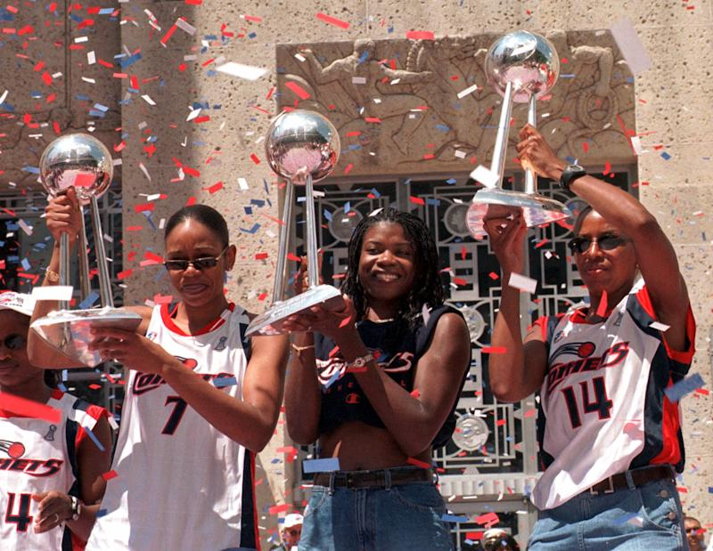 Houston Comets players Tina Thompson, left, Sheryl Swoopes, center, and Cynthia Cooper hoist the Comets' three WNBA championship trophies during a rally after a parade honoring the three-time WNBA champions Wednesday, Sept. 8, 1999, in Houston. (AP Photo/Brett Coomer)