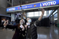 Samantha Jones, left, and Peter Vina take selfies near the Michael Jordan statue on Election Day, Tuesday, Nov. 3, 2020, in the atrium of the United Center, transformed into a super voting site in Chicago. (AP Photo/Charles Rex Arbogast)
