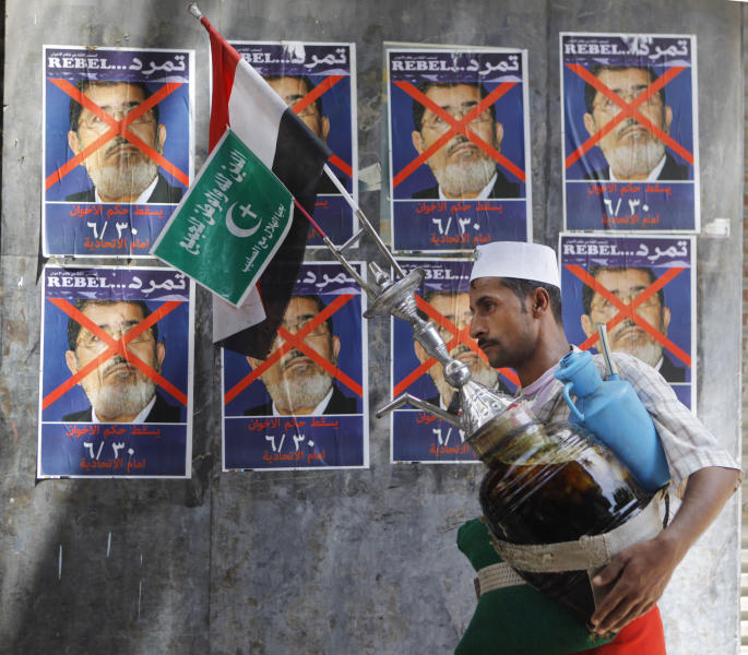 """An Egyptian vendor walks past anti-government posters for a campaign calling for the ouster of Egyptian President Mohammed Morsi and for early presidential elections in Cairo, Egypt, Friday, June 7, 2013. Young activists are trying to rally public discontent with Egypt's Islamist President Mohammed Morsi by fanning out in the streets and collecting millions of signatures on a petition calling for his removal. Morsi's Muslim Brotherhood has dismissed the campaign as irrelevant, even illegal, but the signature drive has stirred up Egypt's politics as the president nears the end of his tumultuous first year in office. The Arabic at the bottom of the poster reads, """"Down with Muslim brotherhood rule. June 30. At the presidential palace."""" The Arabic on the green flag reads, """"Religion is for god, and the nation is for everyone."""" (AP Photo/Amr Nabil)"""