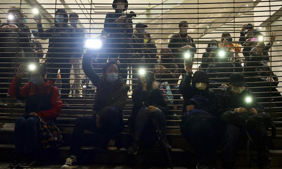 Pro-democracy protesters hold mobile phone lights in the air outside court in Hong Kong
