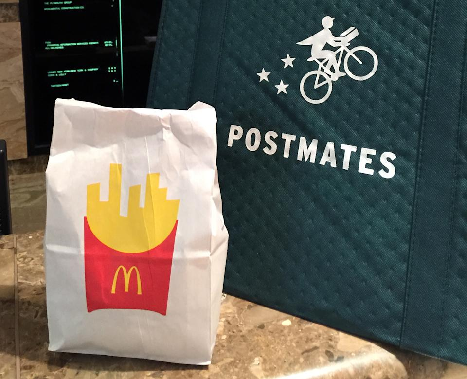 A bag of food from McDonald's ordered through the Postmates service sits next to a Postmates delivery bag during a delivery in New York on Wednesday, May 6, 2015. McDonald's on Monday. May 5, 2015 became the latest chain to announce that it's teaming up with Postmates to offer delivery as a pilot program in New York City, following similar announcements by Chipotle and Starbucks. (AP Photo/Candice Choi)
