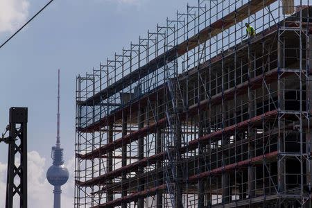 A worker is seen behind scaffoldings at a construction site near the Fernsehturm TV tower in Berlin