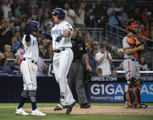 San Diego Padres' Hunter Renfroe, center, celebrates his two-run home run with Freddy Galvis, left, as San Francisco Giants catcher Nick Hundley stands near the plate during the seventh inning of a baseball game in San Diego, Saturday, April, 14, 2018. (AP Photo/Kyusung Gong)
