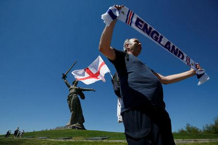 """An England's fan poses in front of """"The Motherland Calls"""" monument at the Mamayev Kurgan World War Two memorial complex in Volgograd"""