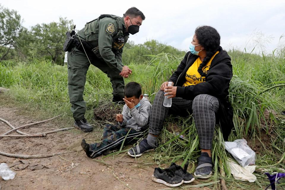 An agent in uniform, left, speaks with a woman seated next to a child