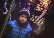 """A boy looks in the window as he lines up outside a Toys""""R""""Us store in Times Square before their Black Friday Sale in New York November 28, 2013. REUTERS/Carlo Allegri"""