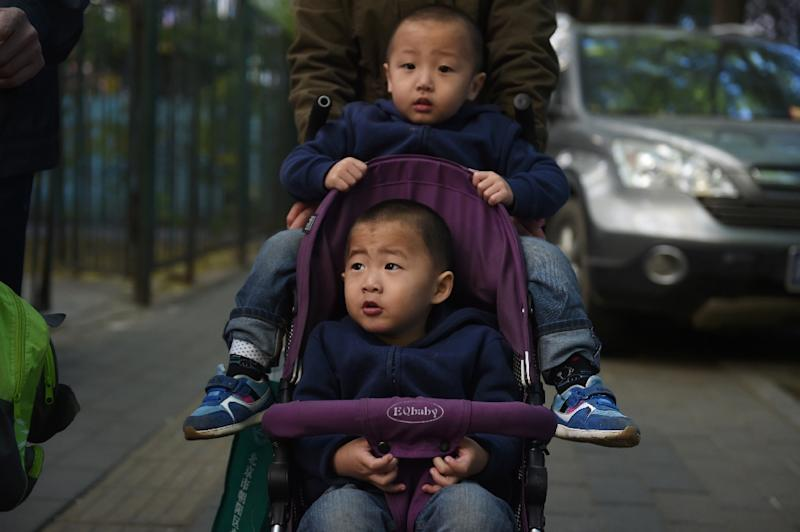 Two brothers are pushed in a pram in Beijing (AFP Photo/Greg Baker )