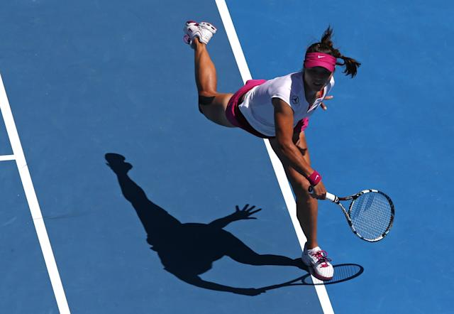 Li Na of China follows through on a shot to Eugenie Bouchard of Canada during their semifinal at the Australian Open tennis championship in Melbourne, Australia, Thursday, Jan. 23, 2014. (AP Photo/Eugene Hoshiko)