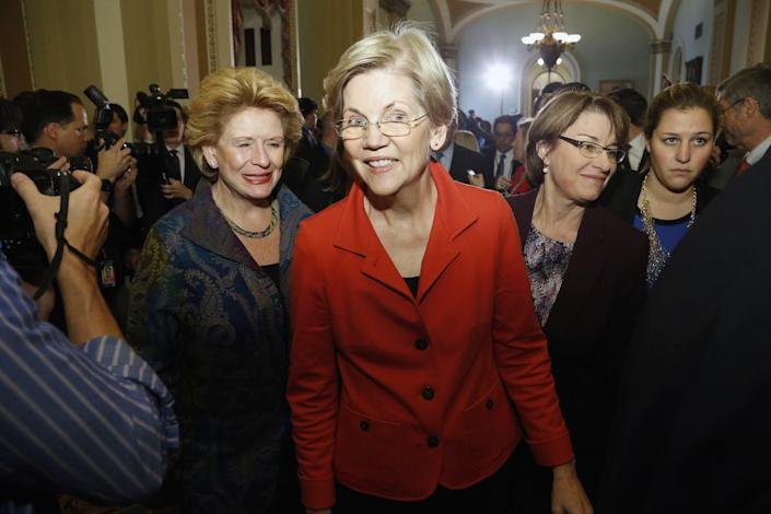 """U.S. Senator Elizabeth Warren (D-MA) (C), flanked by Senator Debbie Stabenow (D-MI) (L) and Senator Amy Klobuchar (D-MN) (R), leaves after speaking to reporters following a leadership election for the 114th Congress on Capitol Hill in Washington in a November 13, 2014 file photo. Backed with $1.25 million from liberal advocacy groups MoveOn.org and Democracy for America, the """"Run Warren Run"""" group has opened offices in New Hampshire and Iowa, hoping she will jump in and contending Warren's message of populist economics could propel her into the White House in 2016. REUTERS/Jonathan Ernst/files (UNITED STATES - Tags: POLITICS)"""