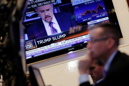 A trader works on the floor of the New York Stock Exchange (NYSE) as news plays on a television in the background shortly after the opening bell in New York, U.S., March 22, 2017.  REUTERS/Lucas Jackson