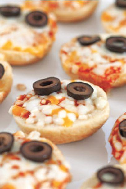 """<p>A few sliced olives turn this finger-food favorite into a yummy Halloween treat. Plus, you can use whatever brand of pizza bite is your favorite.</p><p><em><a href=""""https://www.womansday.com/food-recipes/food-drinks/a28834124/edible-monster-pizza-bites-recipe/"""" rel=""""nofollow noopener"""" target=""""_blank"""" data-ylk=""""slk:Get the Monster Pizza Bites recipe."""" class=""""link rapid-noclick-resp"""">Get the Monster Pizza Bites recipe.</a></em></p>"""