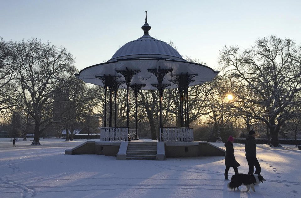 <p>A couple walk their dog through the snow and past the bandstand in Southwark Park in south London. Britons in the south-east and London woke to a thick and freezing blanket of snow this morning after a flurry fell overnight. (AP Photo/Tony Hicks) </p>