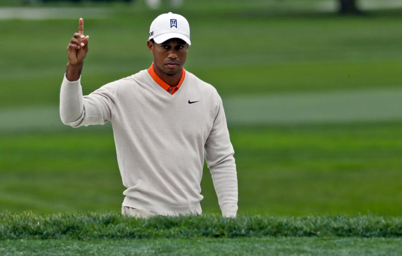 Tiger Woods gestures after his shot out of a bunker on the par-5 sixth hole on the South Course at Torrey Pines goes into the cup for an eagle during the first round of the Farmers Insurance Open golf tournament Thursday Jan. 24, 2013, in San Diego. (AP Photo/Lenny Ignelzi)